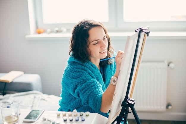 Belle artiste féminine peinture à la maison avec joli sourire et peintures sur le côté