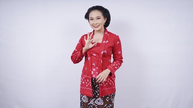 Belle asiatique en geste kebaya ok isolé sur fond blanc