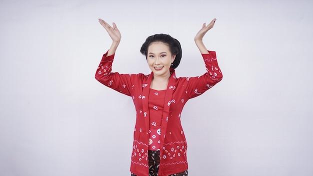 Belle asiatique en kebaya pointant vers le haut isolé sur fond blanc