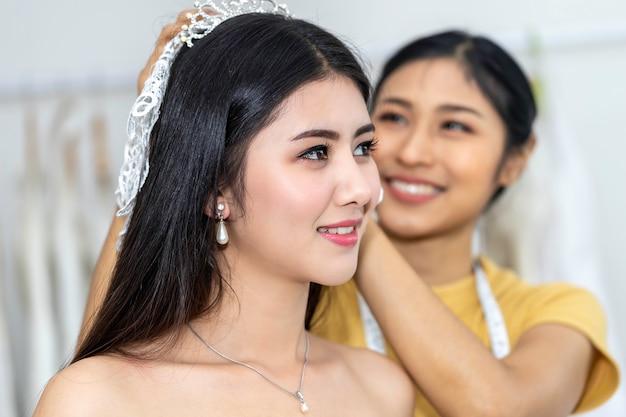 Belle asiatique souriante et essayant la robe de mariée dans un magasin.