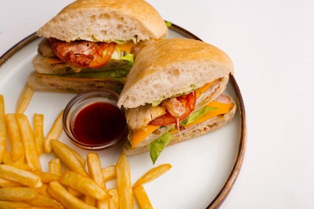Belle assiette avec deux sandwichs, des frites et un petit bol avec de la sauce.