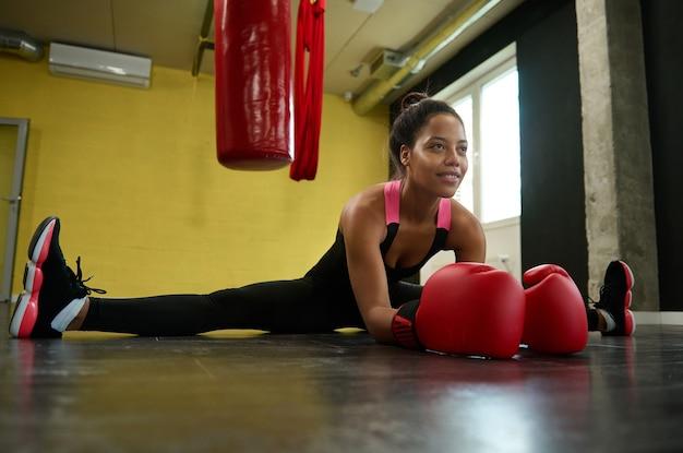 Belle athlète africaine, boxeuse en gants rouges de boxe effectuant une ficelle sur le sol d'une salle de sport avec un sac de boxe de boxe. concept d'étirement, de sport et de bien-être des arts martiaux de combat