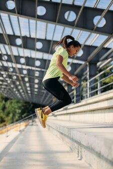 Belle athlète féminine en vêtements de sport sautant tout en faisant de l'exercice dans les escaliers. femme en bonne santé et jeune bénéficiant d'une activité sportive pendant les journées ensoleillées à l'extérieur.