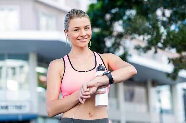 Une belle athlète regarde sa montre