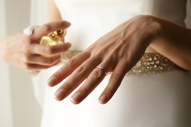 Belle bague de fiançailles mise sur le doigt délicat de la mariée