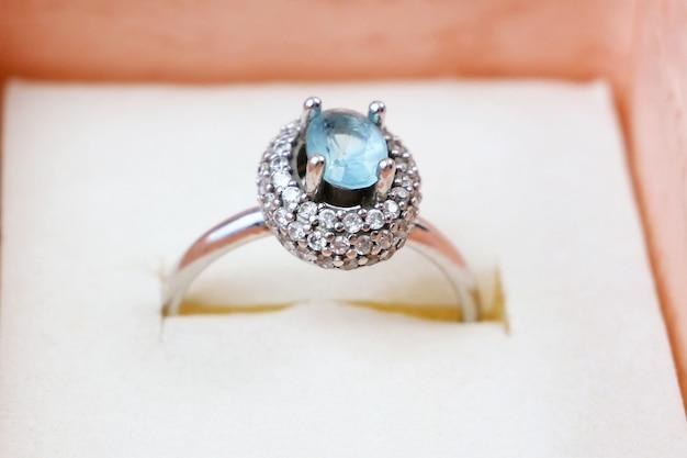 Belle bague avec grosse topaze bleue et diamants dans une boîte cadeau