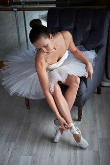 Belle ballerine brune assise sur un fauteuil vintage et ajustant sa chaussure de pointeur. copyspace