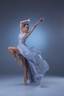 La belle ballerine dansant en longue robe bleue sur fond bleu