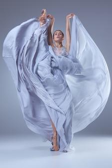 La belle ballerine dansant en longue robe lilas sur fond lilas