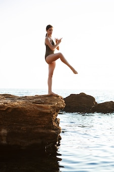 Belle ballerine dansant, posant sur un rocher à la plage