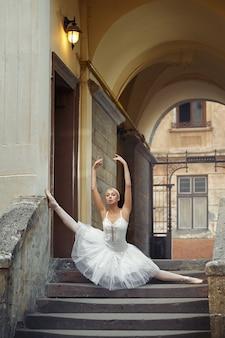 Belle ballerine dansant près d'un vieux bâtiment
