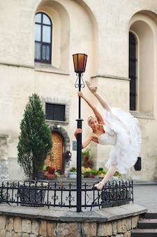 Belle ballerine gracieuse dansant dans les rues d'un vieux ci