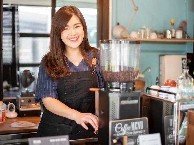 Belle barista sourit dans son café