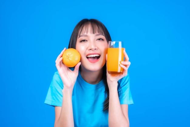 Belle beauté femme asiatique jolie fille avec une coiffure frange en t-shirt bleu se sentir heureux de boire du jus d'orange pour une bonne santé et tenir ou des fruits orange sur fond bleu - mode de vie femme soins de santé