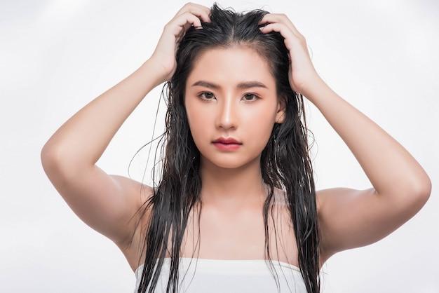Une belle, belle femme attrape ses cheveux en désordre.