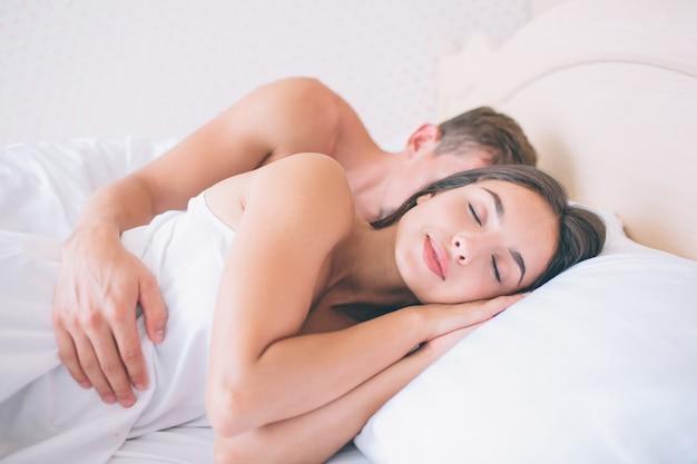 Belle et belle femme dort dans un lit frais et blanc et un homme la serre dans ses bras