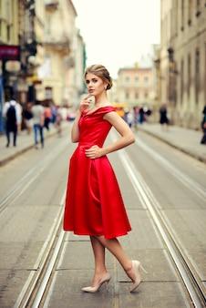 Belle belle femme vêtue d'une robe rouge debout sur les voies de tramway sur la ville