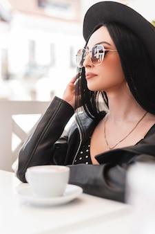 Une belle belle fille à la mode avec des lunettes de soleil et un chapeau dans une veste et une robe en cuir à la mode est assise dans un café et boit un délicieux café