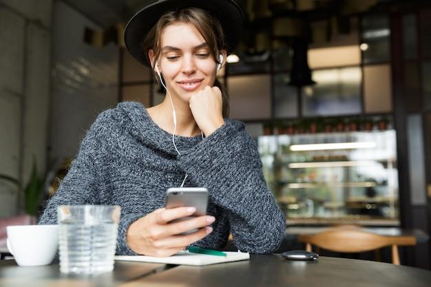 Belle belle jeune femme habillée en pull et chapeau assis dans une chaise à la table du café, écouter de la musique avec des écouteurs, à l'aide de téléphone mobile, intérieur élégant