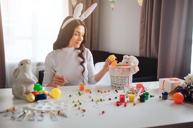 Belle belle jeune femme se prépare pour pâques. elle s'assoit à table et tient un œuf coloré. modèle mis dans un panier avec un lapin. décoration et bonbons sur table.