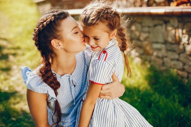 Une belle et belle maman aux cheveux longs dans une robe bleue debout dans un parc solaire et en jouant