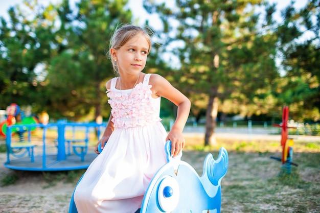 Une belle et belle petite fille dans une magnifique robe longue délicate rose est assise sur une petite balançoire, un parc d'été chaud et ensoleillé en vacances tant attendues