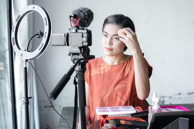 La belle blogueuse asiatique de beauté de mode se penche sur un appareil photo numérique. critique un produit de beauté pour un blog vidéo, parle de produits cosmétiques en tenant une palette de maquillage tout en enregistrant sa vidéo.