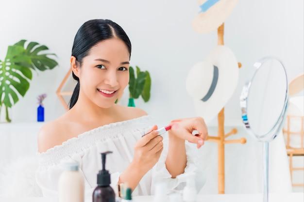 Une belle blogueuse asiatique montre comment se maquiller et utiliser des produits cosmétiques. devant le miroir et la caméra enregistrant une vidéo vlog en direct à la maison. soins de la peau pour un concept de visage sain.