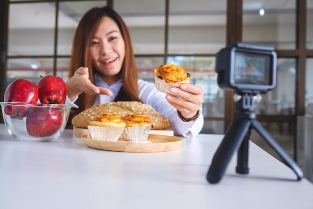 Une belle blogueuse culinaire asiatique ou un vlogger enregistrant une vidéo devant une caméra