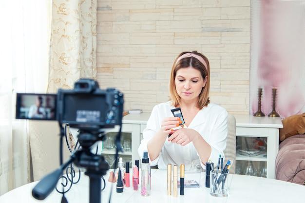 Belle blogueuse femme d'âge moyen montre comment utiliser les cosmétiques. enregistrement de blog vidéo en direct à la maison. la version moderne du travail à la maison.