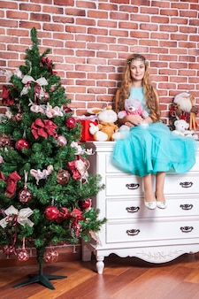 Belle blonde adolescente s'asseoir sur une table de chevet blanche près de l'arbre de noël, avec de nombreux jouets, sourire à pleines dents et regardant la caméra. prise de vue en studio