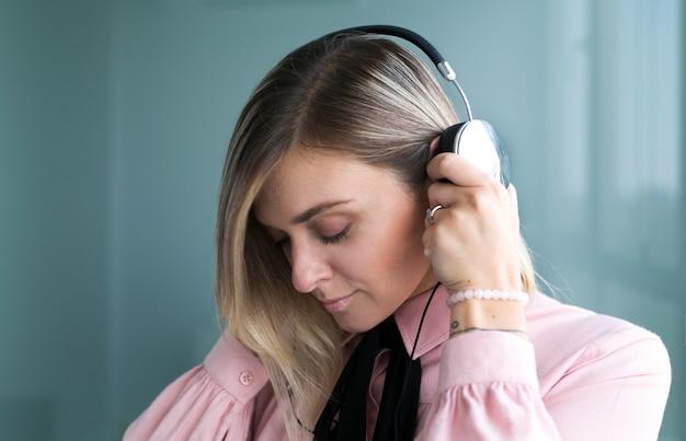 Belle blonde au casque argenté écoute de la musique
