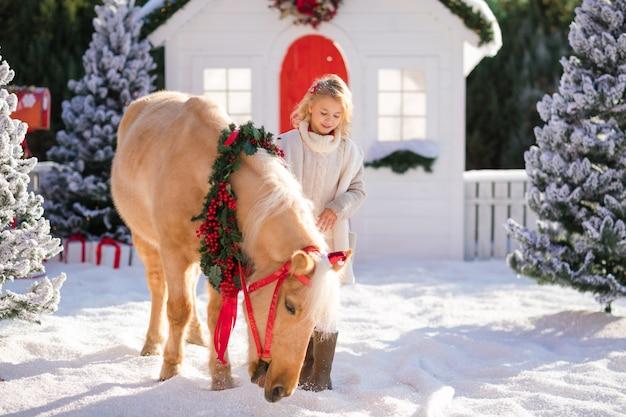 Belle blonde aux cheveux bouclés et adorable poney avec couronne festive près de la petite maison en bois et arbres couverts de neige.