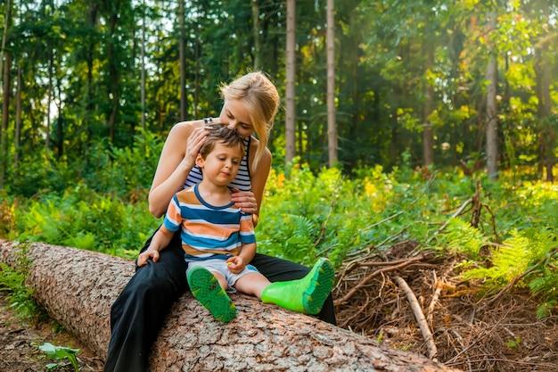 La belle blonde aux cheveux est assise sur une bûche avec son fils en forêt