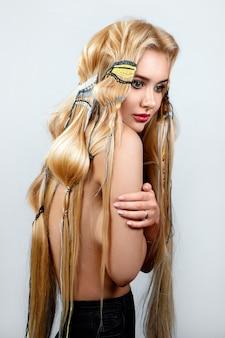 Belle blonde aux cheveux longs, coiffure insolite avec des fils colorés, blanc.