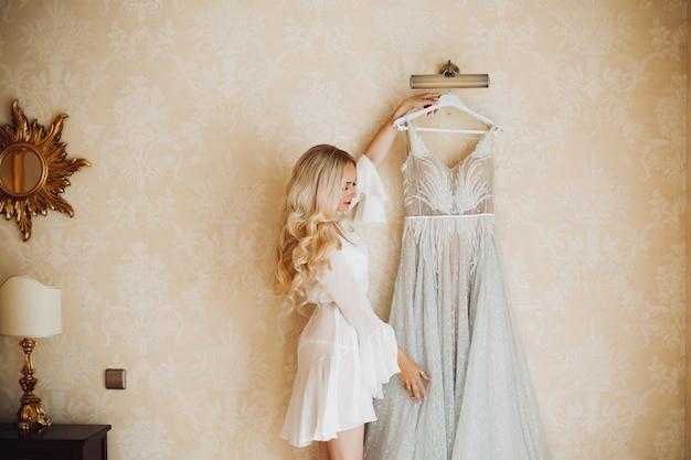 Belle blonde aux cheveux longs mariée avec robe de mariée