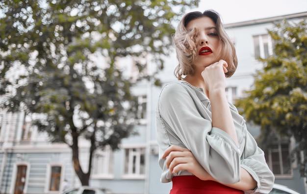 Belle blonde aux lèvres rouges à l'extérieur près du bâtiment fait des gestes avec ses mains émotions copy space. photo de haute qualité