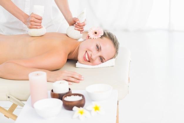 Belle blonde bénéficiant d'un massage aux compresses aux herbes