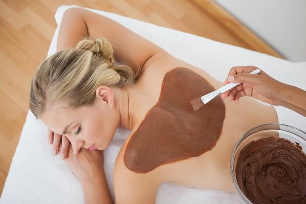 Belle blonde bénéficiant d'un traitement de beauté au chocolat