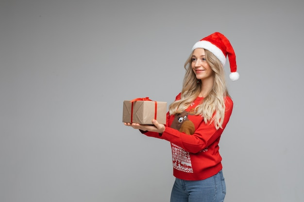 Belle blonde avec un cadeau de noël dans les mains.