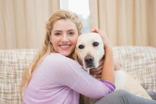 Belle blonde sur le canapé avec chien