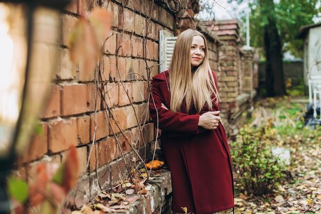 Belle blonde caucasienne portant un manteau profitant de la confortable journée d'automne tout en détournant les yeux et en souriant. femme posant devant la caméra