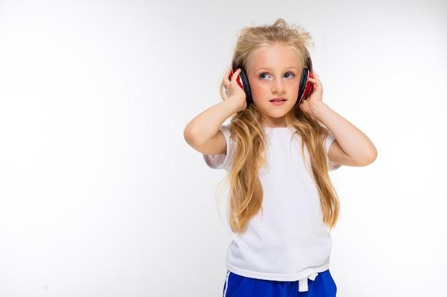 Belle blonde charmante jeune jolie fille dans un look décontracté avec un casque rouge et sur un mur blanc