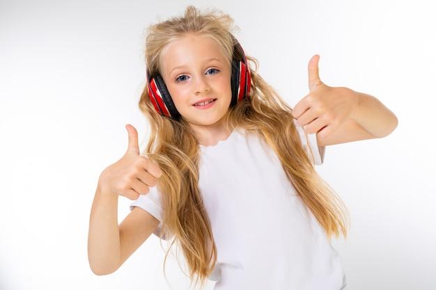Belle blonde charmante jeune jolie fille dans un look décontracté avec des écouteurs rouges en écoutant de la musique et sur un mur blanc