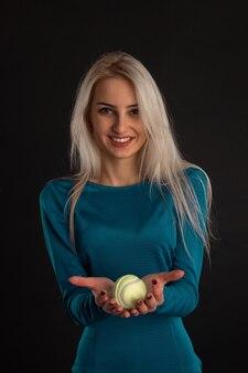 Belle blonde dans une robe bleue avec une balle de tennis sur fond noir
