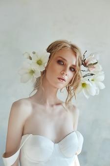 Belle blonde élancée au soleil du soir dans une longue robe blanche. portrait d'une femme avec une fleur. coiffure parfaite et cosmétiques de la mariée