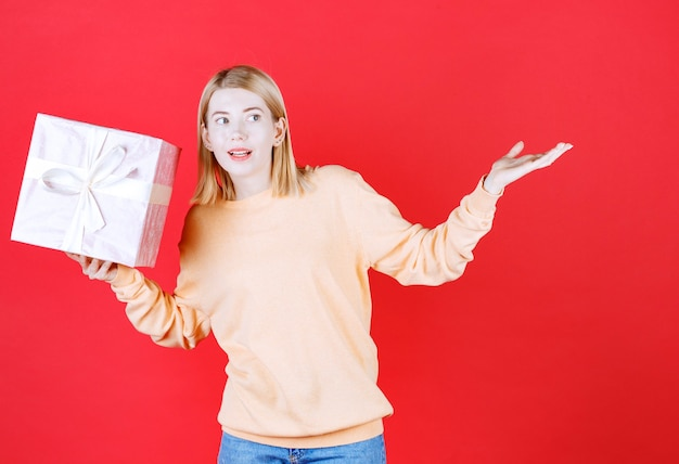 Belle blonde féminine faisant signe de la main et tenant la boîte-cadeau tout en se penchant à son côté droit
