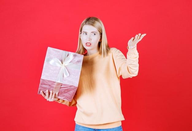 Belle blonde féminine faisant signe de la main tout en tenant la boîte-cadeau devant le mur rouge