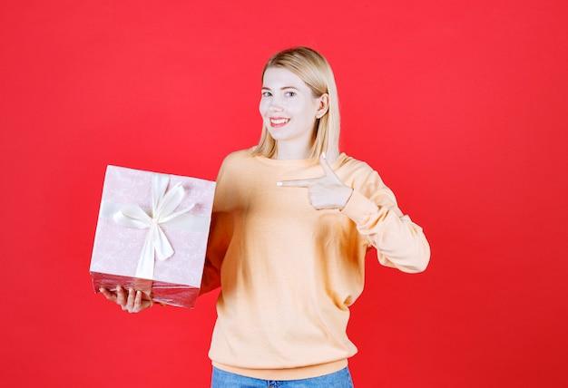 Belle blonde féminine pointant la boîte-cadeau en souriant devant le mur rouge