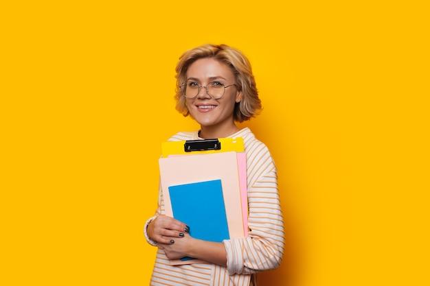 Belle blonde femme caucasienne souriant joyeusement sur fond jaune tout en tenant des livres